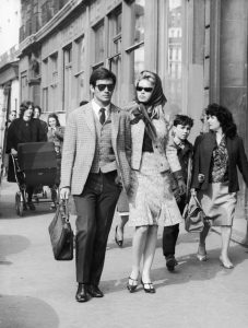 6th April 1962: French actors Sami Frey and Brigitte Bardot are followed by fans as they walk on Boulevard Richard-Lenoir, Paris, France. Both wear dark sunglasses; Bardot wears a kerchief with a tweed skirt suit. (Photo by Agence France Presse/Agence France Presse/Getty Images)